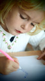 Little blond girl drawing Stock Photos