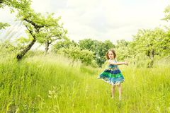 Little blond girl in a dress in the garden. Little girl laughing and having fun. Little blond girl in a dress in the garden. Little girl laughing and having fun Royalty Free Stock Images