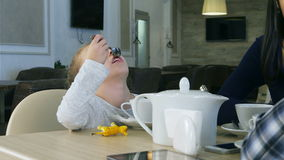 Little blond girl drinking tea sitting in cafe with her lovely parents. stock footage