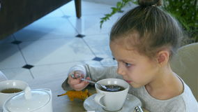 Little blond girl drinking tea from spoon while her parents are busy with tablet. stock video footage