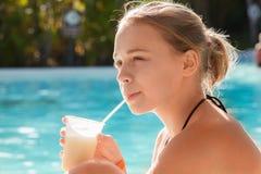 Little blond girl drinks cocktail through plastic tube Stock Image