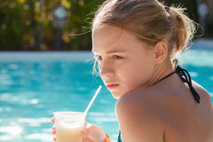 Little blond girl drinks fruit cocktail through plastic tube Stock Images
