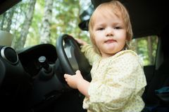 Little blond girl driving car Stock Photos