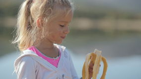 Little blond girl eating a banana next to the lake stock video footage