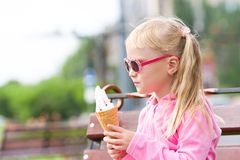 Little blond girl eating ice-cream Stock Images