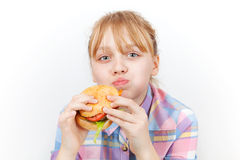 Little blond girl eats burger Stock Image