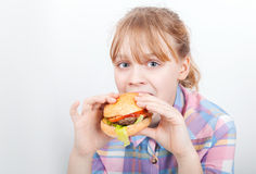 Little blond girl eats hamburger above white Royalty Free Stock Photography