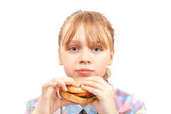 Little blond girl eats hamburger isolated on white Royalty Free Stock Photography