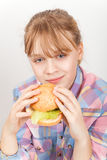 Little blond girl eats homemade burger Stock Photography