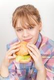 Little blond girl eats homemade burger Stock Photography