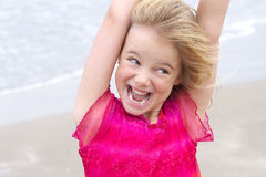 Little blond girl with expressive face. A beautiful little girl making a funny expression at the beach Royalty Free Stock Images