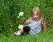 Little blond girl with flowers Royalty Free Stock Images