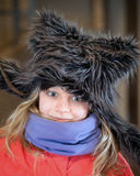 Little blond girl in fun artificial fur hat Royalty Free Stock Images