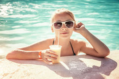 Little blond girl with glass of cocktail in swimming pool Royalty Free Stock Photo