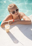 Little blond girl with glass of cocktail in swimming pool Stock Images