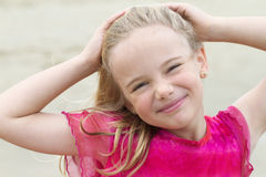 Little blond girl with hands on head Royalty Free Stock Images
