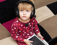 Little blond girl in the headphones with the tablet Stock Photos