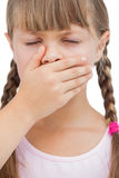 Little blond girl with her hand on her mouth with her eyes close Royalty Free Stock Image