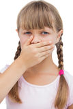 Little blond girl with her hand on her mouth Royalty Free Stock Images
