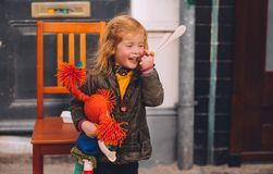 Little blond girl and her orange hair doll on King`s Day festivity, Netherlands Royalty Free Stock Images