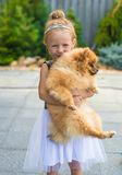 Little blond girl with her pet dog outdoors in Royalty Free Stock Photo