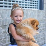 Little blond girl with her pet dog outdoors Stock Photography