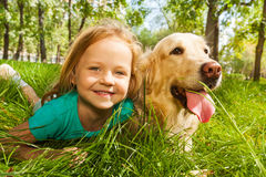 Little blond girl with her retriever dog. Funny wide angle portrait of happy smiling little girl and her happy golden retriever dog pet laying in the grass of Royalty Free Stock Photography