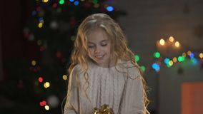 Little blond girl holding present under Christmas tree, magic winter atmosphere. Stock footage stock footage