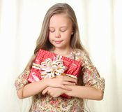 Little blond girl holding a red glamorous gift. With pleasure Royalty Free Stock Images