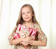 Little blond girl holding a red glamorous gift. And smiling Royalty Free Stock Image