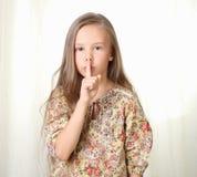 Little blond girl keepeing silence. Holding forefinger near lips Royalty Free Stock Photos