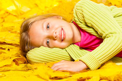 Little blond girl lays on the autumn maple leaves Stock Photography