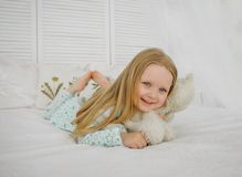A little blond girl lies in bed and hugs a bear. Girl in pajamas, white bed. stock images