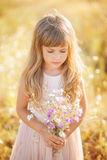 Little blond girl looking at bouquet stock photography