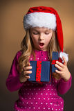 Little blond girl looking surprise with new year present. Royalty Free Stock Images