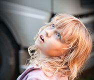 Little blond girl looking up with amazement Stock Photo