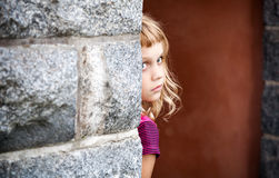Little blond girl looks out from behind stone wall Royalty Free Stock Image