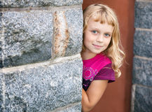 Little blond girl looks out from behind the wall Stock Photos