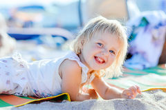 Little blond girl is lying on the beach Royalty Free Stock Images