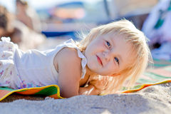 Little blond girl is lying on the beach Stock Images