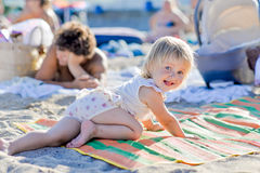 Little blond girl is lying on the beach Royalty Free Stock Image