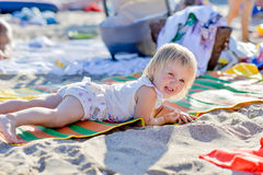 Little blond girl is lying on the beach Royalty Free Stock Photos