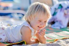 Little blond girl is lying on the beach Stock Photos