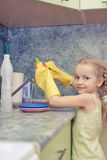 Little girl cleaning things ware with water and gel Royalty Free Stock Images