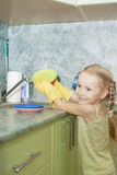 Little girl cleaning things ware with water and gel Royalty Free Stock Photos