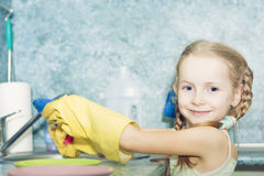 Little preschooler girl makes kitchen dishes cleaning Stock Photography
