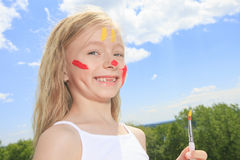 Little blond girl with paint on the face Stock Images