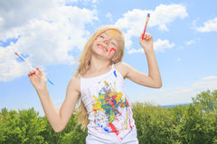 Little blond girl with paint on the face Stock Photo