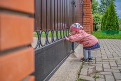 A little blond girl peers out through the bars of the gate. A happy curious baby is exploring the world with interest stock photo