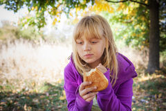 Little blond girl on a picnic in autumn park Stock Images